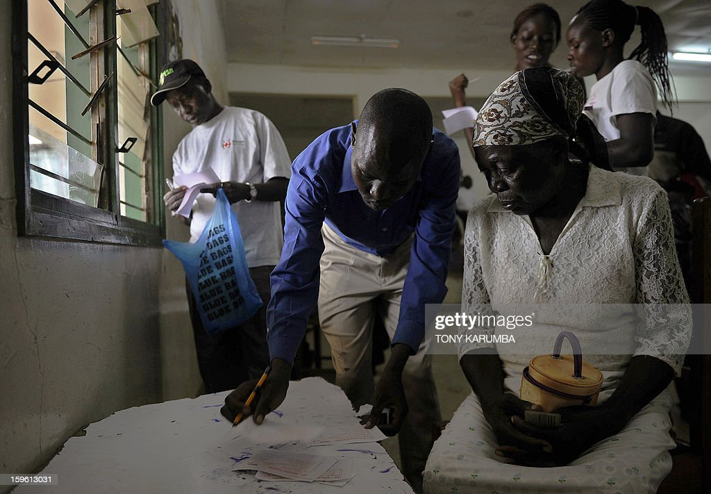 An elderly Kenyan woman is assisted by an election official in filling out ballot forms as she votes in political party primary nominations on January 17, 2013, in the lakeside town of Kisumu, ahead of this year's general election to be held in March. The March 2013 elections are the first since the bloody 2007-08 polls that left at least 1,100 killed and 600,000 more displaced after what began as protests over the election results degenerated into vicious killings pitting supporters of Prime Minister Raila Odinga against those of the outgoing president Mwai Kibaki. AFP PHOTO / Tony KARUMBA