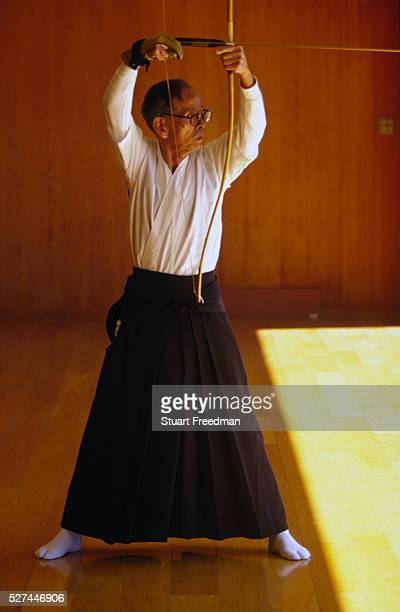 An elderly Kyodo practitioner draws his bow at a Kyoto dojo Kyudo is a modern Japanese martial art derived from ancient Samurai archery and heavily...