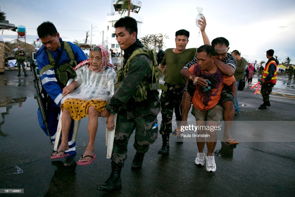An elderly lady and an injured man are carried to a waiting C130 aircraft during the evacuation of hundreds of survivors of Typhoon Haiyan on...