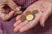An elderly lady holds a few cents of euro in her hands.