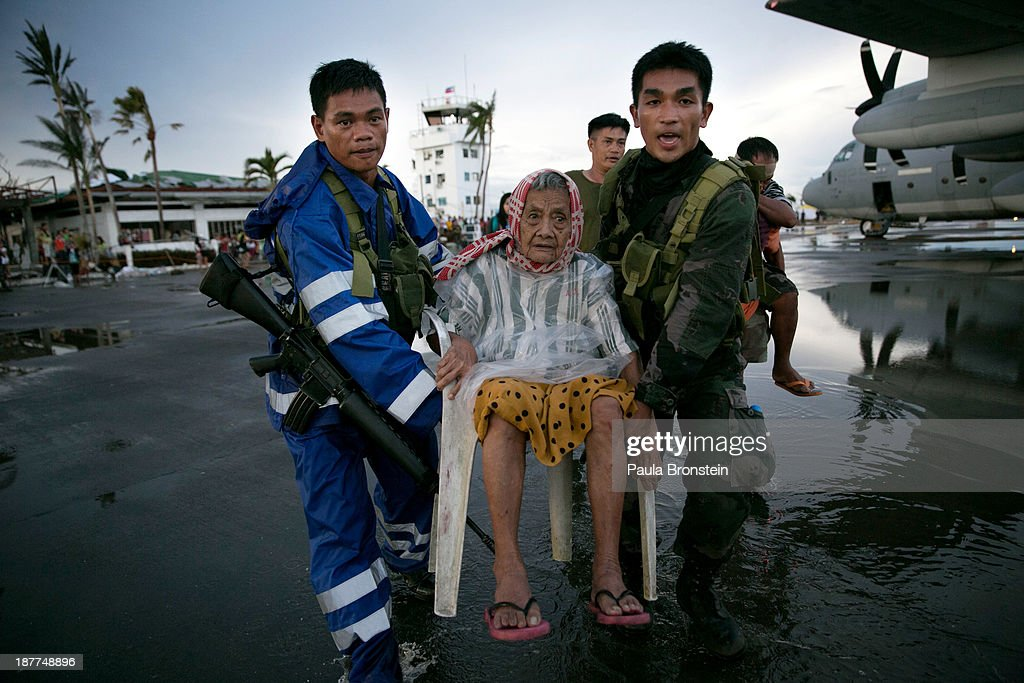 An elderly lady is carried to a waiting C130 aircraft during the evacuation of hundreds of survivors of Typhoon Haiyan on November 12 2013 in...