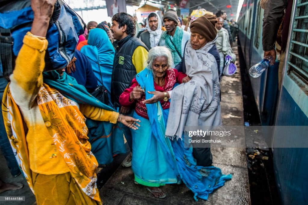 An elderly lady is helped along the platform as Hindu devotees board their train at Allahabad train station, the site of last night's stampede, during the Maha Kumbh Mela on February 11, 2013 in Allahabad, India. According to a government sources report, at least 36 people died in a stampede on a stair case as a train was pulling up on the busiest day of the Maha Kumbh Mela. The Maha Kumbh Mela, believed to be the largest religious gathering on earth, is held every 12 years on the banks of Sangam, the confluence of the holy rivers Ganga, Yamuna and the mythical Saraswati. The Kumbh Mela alternates between the cities of Nasik, Allahabad, Ujjain and Haridwar every three years. The Maha Kumbh Mela celebrated at the holy site of Sangam in Allahabad, is the largest and holiest, celebrated over 55 days, and is expected to attract over 100 million people.