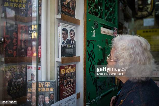 An elderly lady looks at a book in a shop display cabinet of the Causeway Bay Books store featuring Chinese President Xi Jinping and former Chinese...