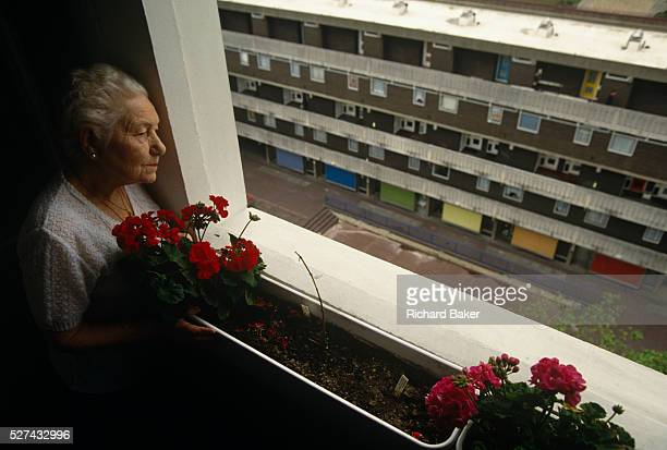 An elderly lady resident of a tower block watches the outside world from her highrise window overlooking the Middlesex Estate in the City of London A...