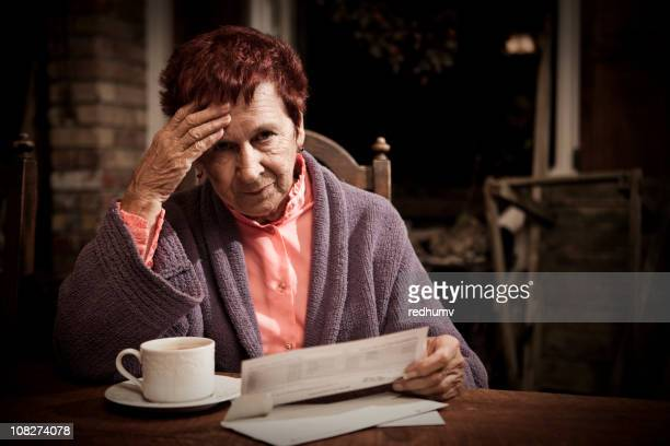 An elderly lady sat looking stressed reading bills