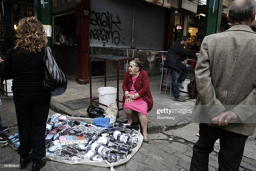 An elderly lady sits on a roadside waiting to sell socks at her street stall in the Kapani district market in Thessaloniki, Greece, on Wednesday, Nov. 13, 2013. Greece 'is following a fiscal adjustment program that aims to make the country's public finances sustainable on a permanent basis,' Finance Minister Yannis Stournaras told lawmakers during the debate, after holding talks with the troika earlier in the week. Photographer: Konstantinos Tsakalidis/Bloomberg via Getty Images