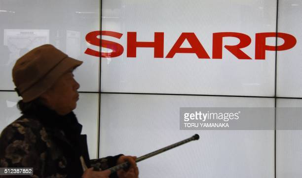 An elderly lady walks before a logo of Japan's electronics giant Sharp in Tokyo on February 26 2016 Japan's centuryold Sharp agreed to be taken over...