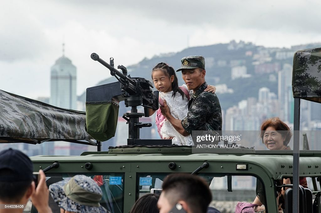 An elderly lady (R) watches as her young relative (C) is held by a PLA soldier as she looks through the iron sight of a gun during the open day of the Chinese People's Liberation Army (PLA) Navy Base at Stonecutter Island in Hong Kong on July 1, 2016, to mark the 19th anniversary of the Hong Kong handover to China . / AFP / Anthony Wallace