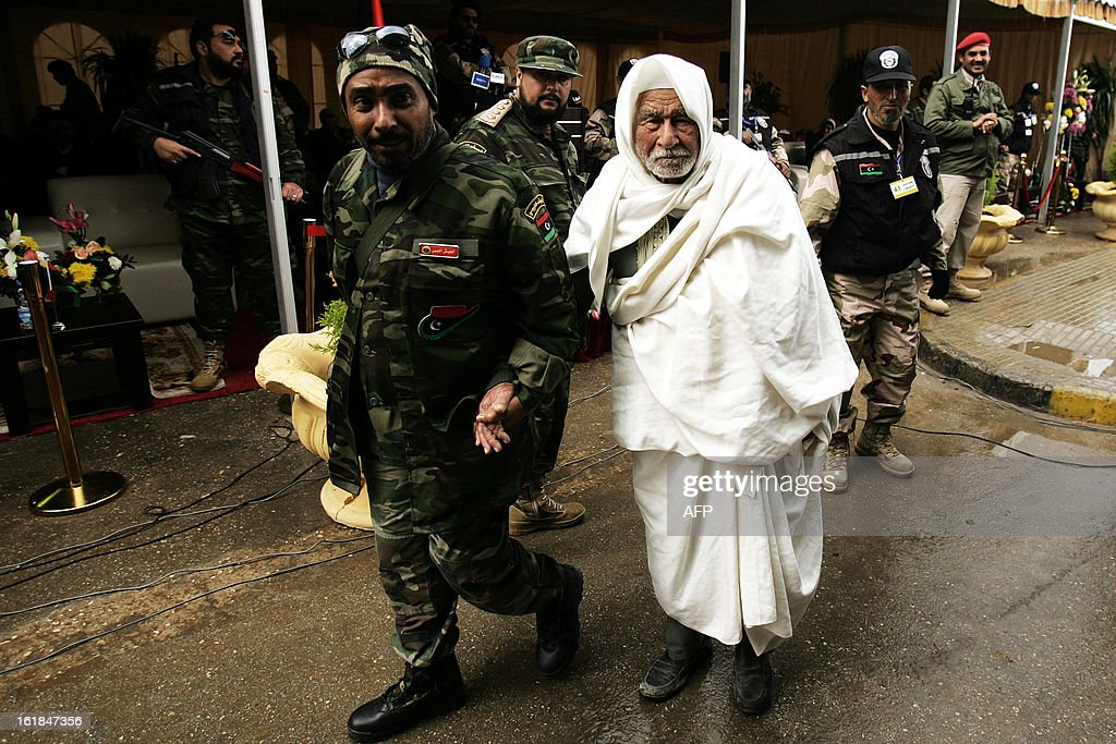 An elderly Libyan man (R) who fought against the Italian colonial rule is escorted by a Libyan soldier upon his arrival to attend a ceremony marking the second anniversary of the start of the Libyan revolution at Tahrir Square in Benghazi on February 17, 2013. Security forces were on high alert across Libya as the north African nation marked two years since the start of the revolt that toppled Moamer Kadhafi after four decades of iron rule. AFP PHOTO/ABDULLAH DOMA