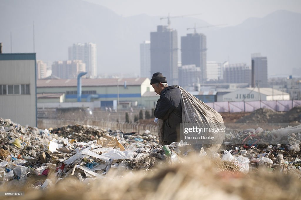 An elderly male migrant worker carries a large bag of plastic bottles he had collected at the Dalian Jinzhou garbage dump. China does not have a recycling infrastructure in many major cities. Many migrant workers search garbage dumps like this one for anything that can be sold. Dalian, China 10 January 2008.
