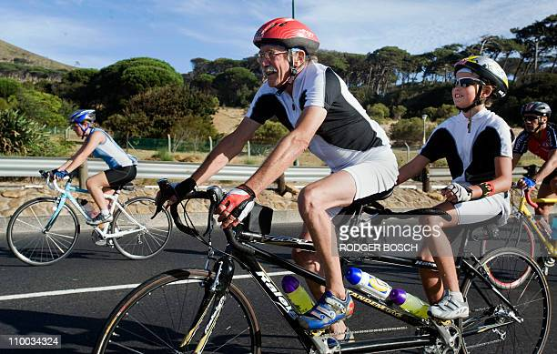 An elderly man and a young boy ride a tandem bicycle in the Argus Cycle Tour on March 13 in Cape Town The tour which runs more than 110 km starts in...