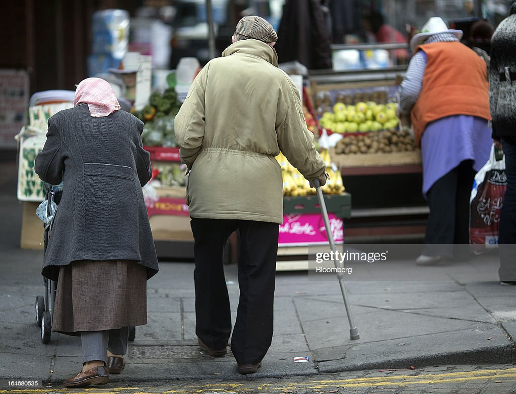 An elderly man and woman make their way past market stalls in Moore Street in Dublin, Ireland, on Saturday, March 16, 2013. Ireland's renewed competiveness makes it a beacon for the U.S. companies such as EBay, Google Inc. and Facebook Inc., which have expanded their operations in the country over the past two years. Photographer: Simon Dawson/Bloomberg via Getty Images