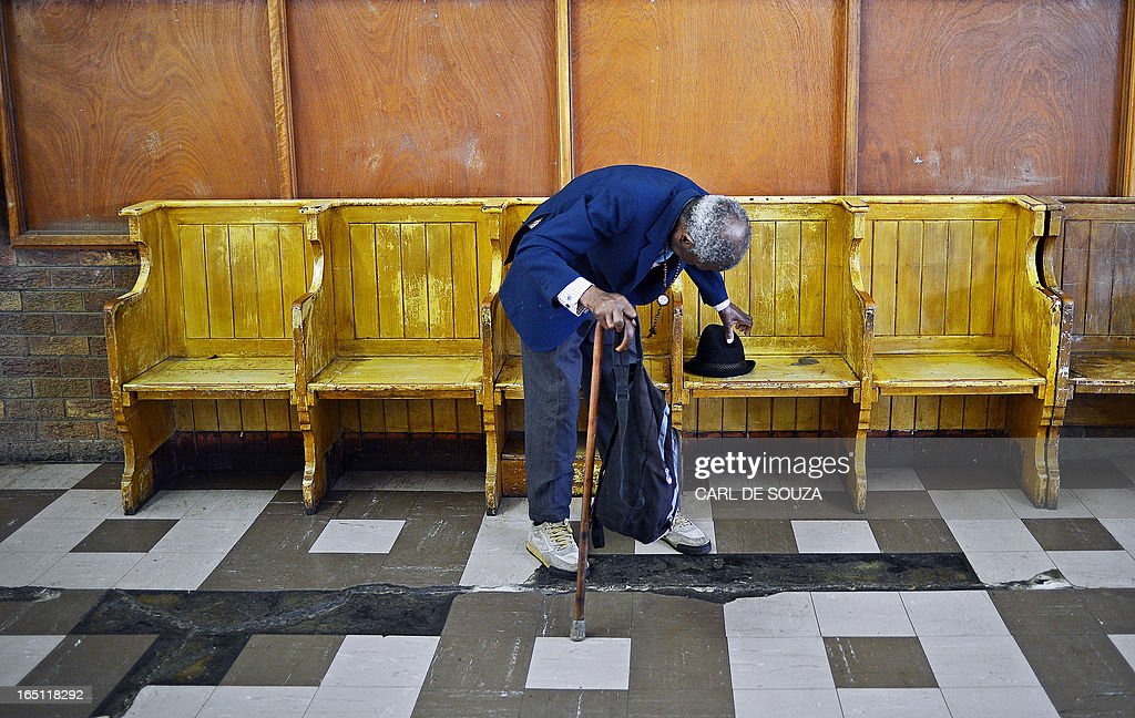 An elderly man arrives to pray at Regina Mundi church in Soweto on March 31, 2013. Regina Mundi church is situated near former South African president Nelson Mandela's old residence and is known for its involvement during the struggle against apartheid. Mandela is spending his fourth day in hospital after making 'steady progress' for a recurring lung infection. The 94 year old is idolised in his home nation. It is the second time within a month that he has been admitted to hospital, after spending a night for check-ups on March 9, 2013. AFP PHOTO / Carl de Souza