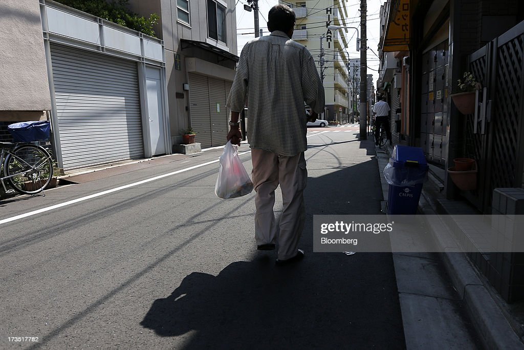 An elderly man carries a bag of groceries as he walks down a street in Tokyo, Japan, on Monday, July 8, 2013. The number of Japanese seniors living alone will rise 54 percent to 7.17 million in 2030 from 4.66 million in 2010, according to the National Institute of Population and Social Security Research, set up by the Ministry of Health, Labour and Welfare. To manage the costs stemming from the aging society, the government aims to push back the pension age to 65 from 60 in stages through 2025. Photographer: Kiyoshi Ota/Bloomberg via Getty Images