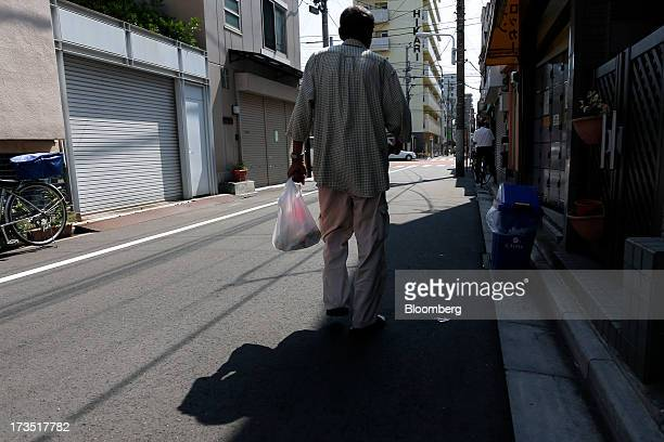 An elderly man carries a bag of groceries as he walks down a street in Tokyo Japan on Monday July 8 2013 The number of Japanese seniors living alone...