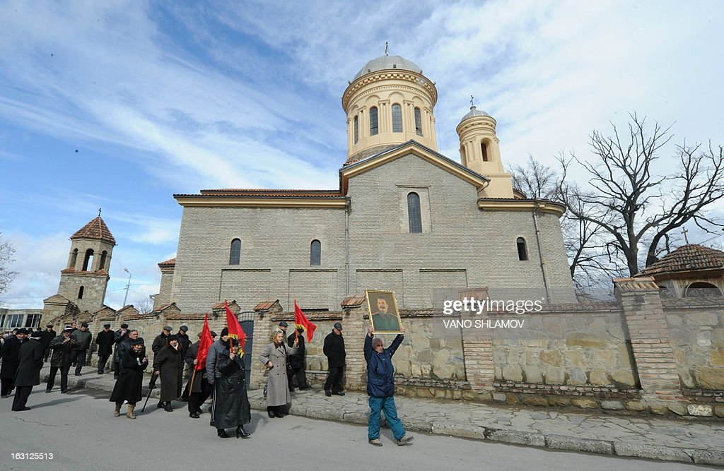 An elderly man carries a portrait of Soviet dictator Joseph Stalin while walking past a church in Stalin's native town of Gori, some 80 km from the capital Tbilisi, on March 5, 2013, during ceremonies to mark the 60th anniversary of Stalin's death. Russia marks today 60 years since the death of Stalin with attitudes split about whether to view him as a tyrant who slaughtered millions or a national saviour who helped turn the country into a global superpower that emerged victorious in World War II. AFP PHOTO /VANO SHLAMOV