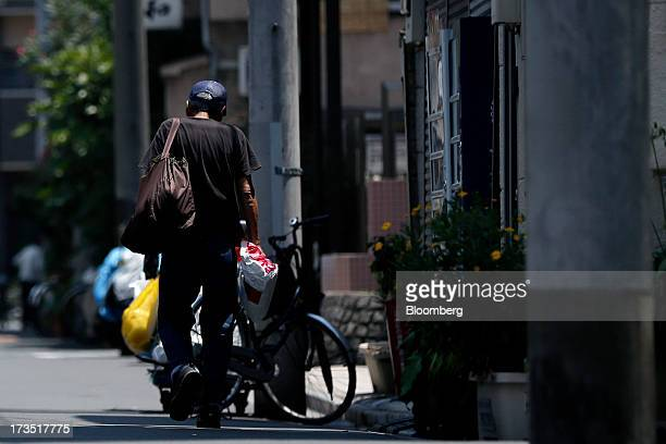 An elderly man carries bags as he walks towards a labor and welfare center in Tokyo Japan on Monday July 8 2013 The number of Japanese seniors living...