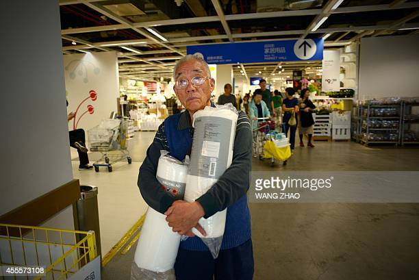 An elderly man carries goods as he walks to the cashier desk near the exit of a mall in Beijing on September 17 2014 Chinese consumer prices rose 20...