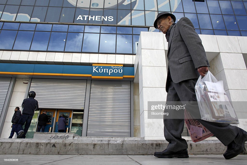 An elderly man carries shopping bags past automated teller machines (ATM) at a shuttered bank branch at the headquarters of the Bank of Cyprus Plc in Athens, Greece, on Tuesday, March 19, 2013. Cyprus's passage of an unprecedented levy on bank deposits was in doubt as euro-area finance ministers responded to criticism of the measure by loosening their stance on how the money is raised. Photographer: Kostas Tsironis/Bloomberg via Getty Images