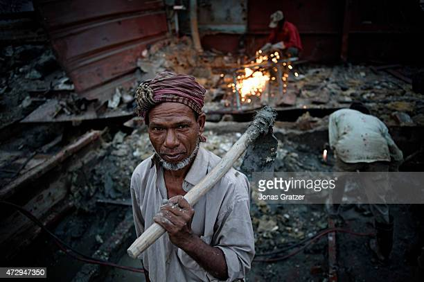 An elderly man carrying a shovel as he walks away from the scrapyard on the beach where mega ships that are out of service are being disassemble for...