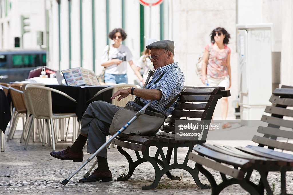 An elderly man checks the time while waiting on a public bench in Lisbon, Portugal, on Wednesday, July 3, 2013. Portuguese borrowing costs topped 8 percent for the first time this year after two ministers quit, signaling the government will struggle to implement further budget cuts as its bailout program enters its final 12 months. Photographer: Mario Proenca/Bloomberg via Getty Images
