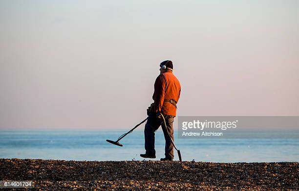 An elderly man dressed in a winter coat and hat beach combing with a metal detector and a spade on Folkestone Beach United Kingdom 19th January 2016