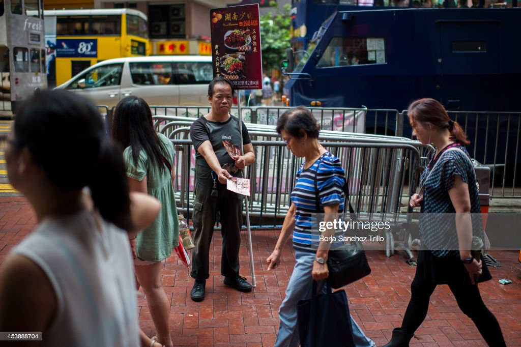 An elderly man gives flyers to the pedestrians on August 20, 2014 in Hong Kong, Hong Kong. A government-commissioned study headed by University of Hong Kong academic Nelson Chow Wing-sun proposed to fund HK $3,000 a month pension for every Hongkonger over 65, rich or poor, without a means test. The pension should be funded partly by contributions ranging from 1 to 2.5 per cent of employees' salaries, paid by employers and workers. One in three old people in Hong Kong lives below estimated poverty line some of them struggling to make a living collecting cardboard boxes and plastic bottles on the street.