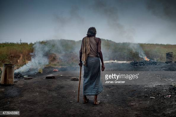An elderly man goes through his village where methane and other toxic gases spew from open wounds of the Earth's crust near the coal mines in Jharia...
