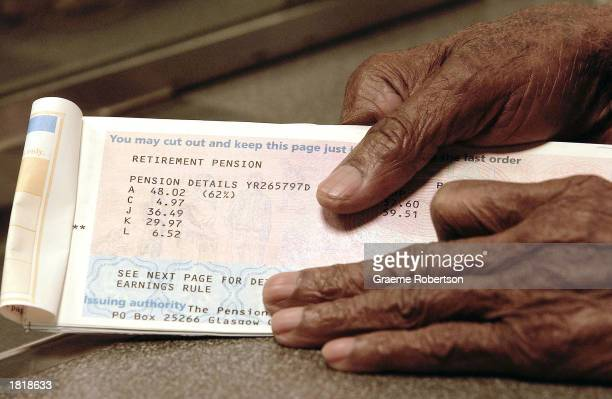 An elderly man handles in his pension book at the post office February 27 2003 in London Although employees' contributions to pensions have risen by...
