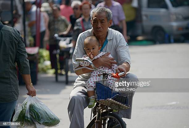 An elderly man holds a baby in his arms as he rides a bicycle along a road in Beijing on September 8 2015 China on September 7 lowered its GDP growth...