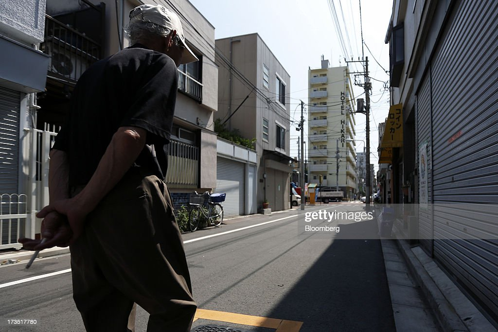 An elderly man holds a lit cigarette as he walks down a street in Tokyo, Japan, on Monday, July 8, 2013. The number of Japanese seniors living alone will rise 54 percent to 7.17 million in 2030 from 4.66 million in 2010, according to the National Institute of Population and Social Security Research, set up by the Ministry of Health, Labour and Welfare. To manage the costs stemming from the aging society, the government aims to push back the pension age to 65 from 60 in stages through 2025. Photographer: Kiyoshi Ota/Bloomberg via Getty Images