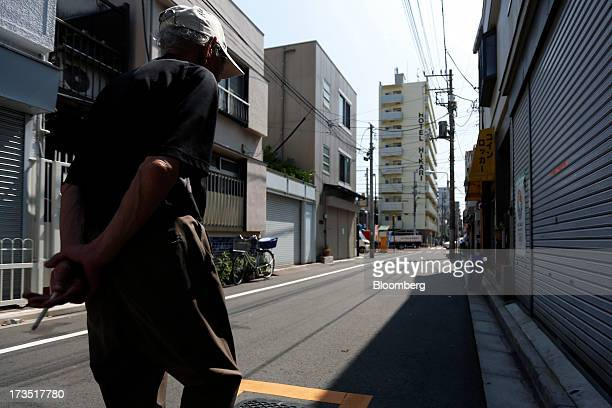 An elderly man holds a lit cigarette as he walks down a street in Tokyo Japan on Monday July 8 2013 The number of Japanese seniors living alone will...