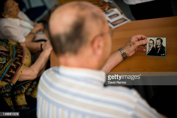 An elderly man holds a portrait of Laurel and Hardy during a memory activity at the Cuidem La Memoria elderly home which specializes in Alzheimer...