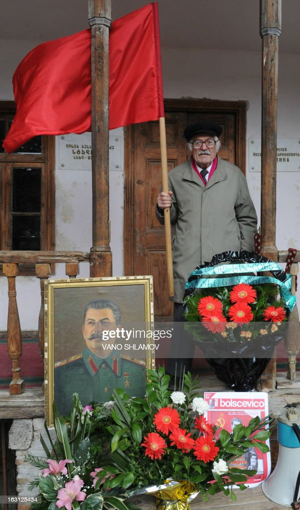 An elderly man holds a red flag as he stands near a portrait of Soviet dictator Joseph Stalin during a rally in Stalin's native town of Gori, some 80 km from the capital Tbilisi, on March 5, 2013, to mark the 60th anniversary of Stalin's death. Russia marks today 60 years since the death of Stalin with attitudes split about whether to view him as a tyrant who slaughtered millions or a national saviour who helped turn the country into a global superpower that emerged victorious in World War II.