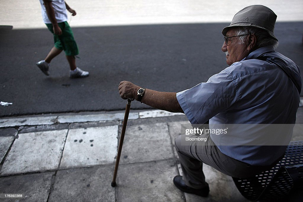 An elderly man holds a walking stick as he sits and waits at a bus shelter in Athens, Greece, on Saturday, Aug. 10, 2013. Greece's economy contracted for a 20th quarter, extending an economic slump that has left more than six in 10 young Greeks out of work. Photographer: Angelos Tzortzinis/Bloomberg via Getty Images