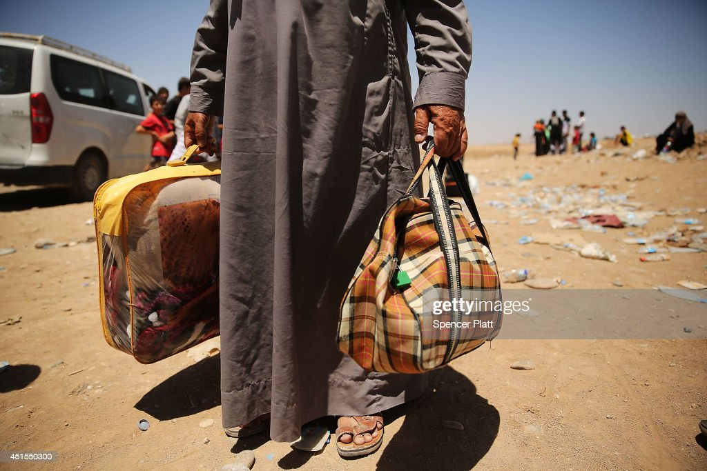 An elderly man holds his bags as over 1000 Iraqis who have fled fighting in and around the city of Mosul and Tal Afar wait at a Kurdish checkpoint in the hopes of entering a temporary displacement camp on July 1, 2014 in Khazair, Iraq. The families, many with small and sick children, had no shelter and little water and food. The displacement camp Khazair is now home to an estimated 1,500 internally displaced persons (IDP's) with the number rising daily. Tens of thousands of people have fled Iraq's second largest city of Mosul after it was overrun by ISIS (Islamic State of Iraq and Syria) militants. Many have been temporarily housed at various IDP camps around the region including the area close to Erbil, as they hope to enter the safety of the nearby Kurdish region.