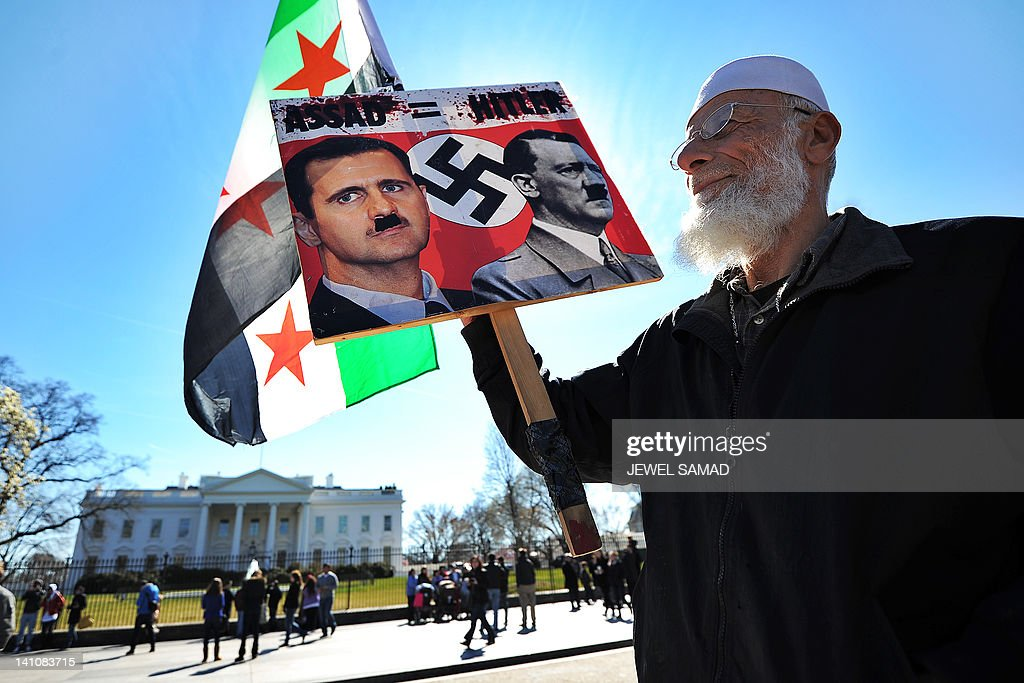An elderly man holds up a placard depicting Syrian president Bashar al-Assad as late German dictator Adolf Hitler during a demonstration against the Syrian president in front of the White House in Washington, DC, on March 10, 2012. At least 62 persons, mostly soldiers and rebels, were killed in violence across Syria on March 10, the first of a two-day visit by international peace envoy Kofi Annan, a monitor said. Annan was in Damascus seeking an end to a year-long crackdown on dissent that has cost an estimated more than 8,500 lives in what was described as positive talks with Assad. AFP PHOTO/Jewel Samad