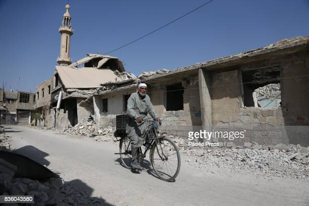 An elderly man is riding a bicycle on a destroyed street in Zamalek in the eastern Ghouta and the area is under the control of the Syrian opposition