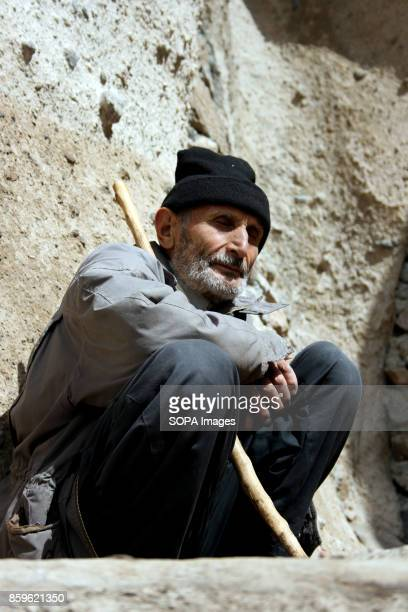 An elderly man is seen sitting front of his house during the day time The tiny village of Kandovan in the Iranian East Azerbaijan Province is known...