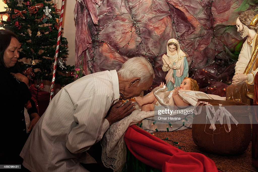 An elderly man kisses the foot of a doll-like figure of the infant Jesus inside the church of Our Lady of the Assumption on December 25, 2013 in Battambang, Cambodia. The parish at Battambang dates back to 1790 when the Catholic community first arrived. Now they serve around 1000 Catholics and 600 families.