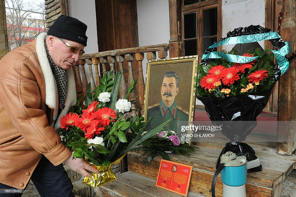 An elderly man lays flowers at a portrait of Soviet dictator Joseph Stalin during a rally in Stalin's native town of Gori, some 80 km from the capital Tbilisi, on March 5, 2013, to mark the 60th anniversary of Stalin's death. Russia marks today 60 years since the death of Stalin with attitudes split about whether to view him as a tyrant who slaughtered millions or a national saviour who helped turn the country into a global superpower that emerged victorious in World War II.