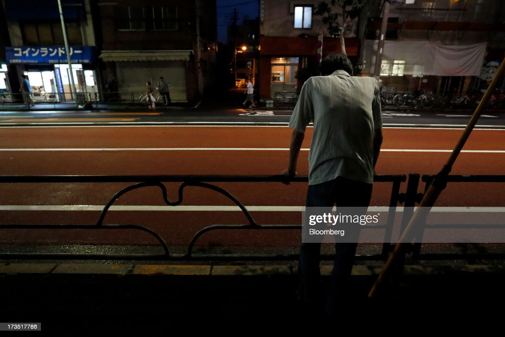 An elderly man leans on a railing along the side of a street at night in Tokyo, Japan, on Monday, July 8, 2013. The number of Japanese seniors living alone will rise 54 percent to 7.17 million in 2030 from 4.66 million in 2010, according to the National Institute of Population and Social Security Research, set up by the Ministry of Health, Labour and Welfare. To manage the costs stemming from the aging society, the government aims to push back the pension age to 65 from 60 in stages through 2025. Photographer: Kiyoshi Ota/Bloomberg via Getty Images