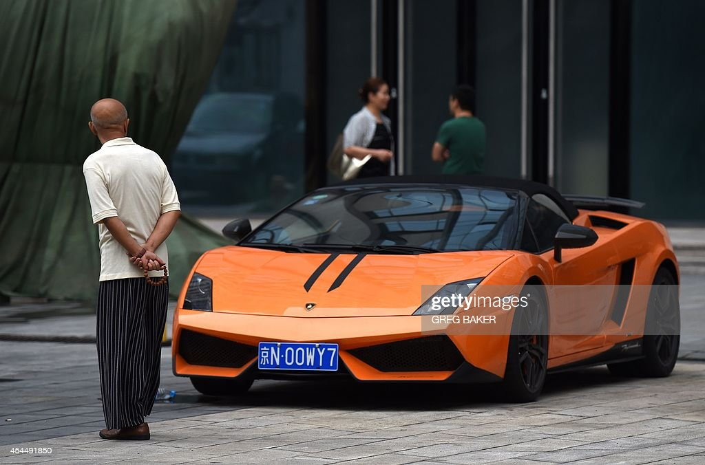 An elderly man looks at a convertible Lamborghini in a car park in Beijing on September 2 2014 China has enjoyed a decadeslong economic boom but at...