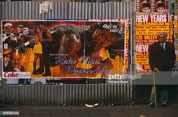 An elderly man of SouthAsian descent stands waiting for a bus in Southall West London To his right is a Bollywood actionhero poster the toughman...