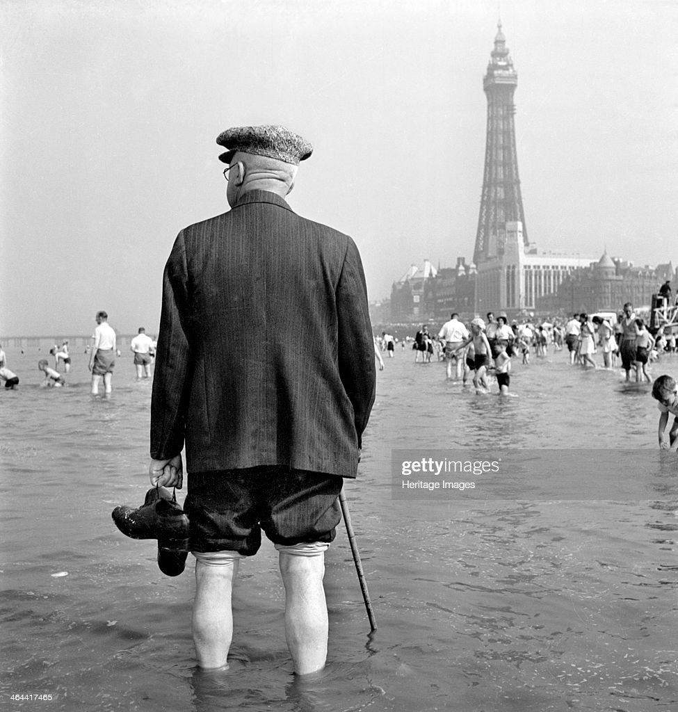 An elderly man paddling in the sea at Blackpool, c1946-c1955; with the Blackpool Tower in the background..
