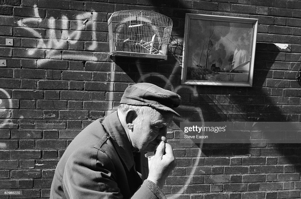 An elderly man passes items for sale at a street market in Brick Lane, east London, March 1993.