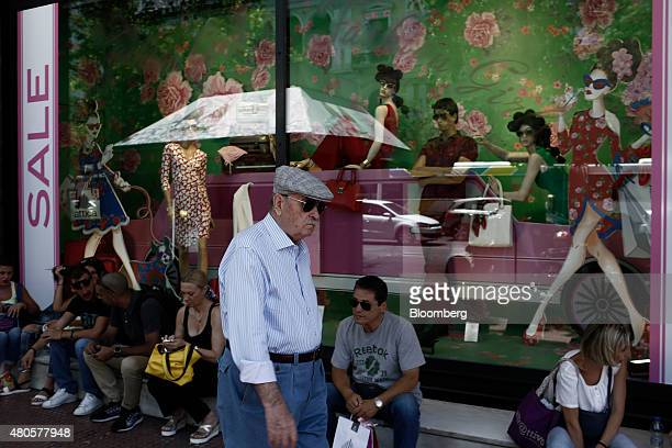 An elderly man passes pedestrians sitting outside a fashion store advertising price discounts in the summer sales in Athens Greece on Monday July 13...