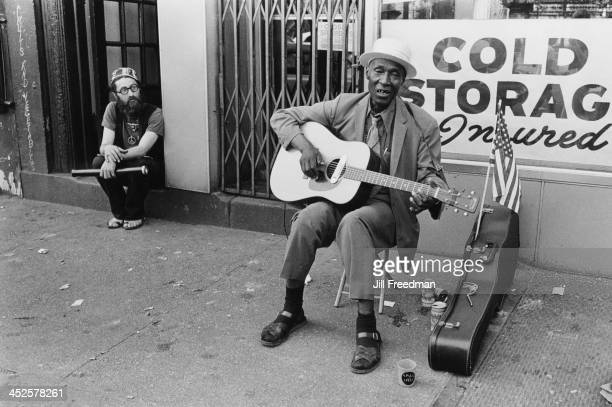 An elderly man plays the guitar on the street in Greenwich Village New York City 1970