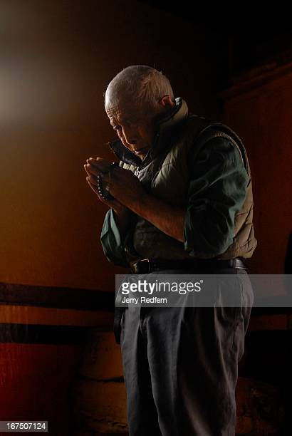 An elderly man prostrates himself before Buddhist icons at the Druk Sangag Choling Monastery in Darjeeling India It is the main seat of the Drukpa...