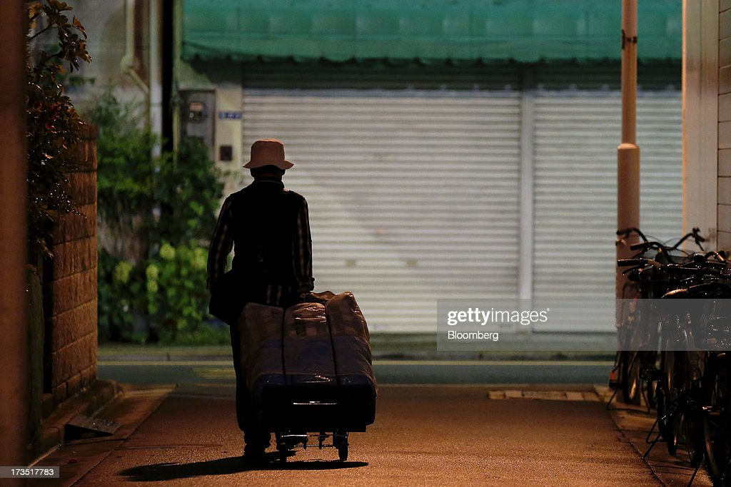 An elderly man pulls a cart as he walks through an alley at night in Tokyo, Japan, on Monday, July 8, 2013. The number of Japanese seniors living alone will rise 54 percent to 7.17 million in 2030 from 4.66 million in 2010, according to the National Institute of Population and Social Security Research, set up by the Ministry of Health, Labour and Welfare. To manage the costs stemming from the aging society, the government aims to push back the pension age to 65 from 60 in stages through 2025. Photographer: Kiyoshi Ota/Bloomberg via Getty Images